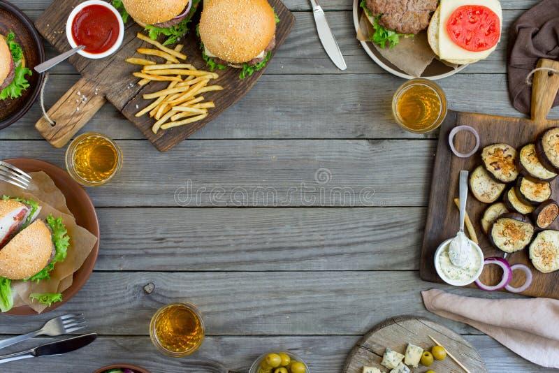 Ram från olika hamburgare och mellanmål på trätabellen royaltyfria bilder