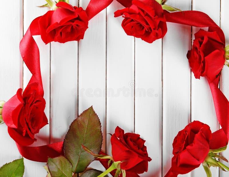 Ram som göras av härliga röda rosor och band på vit träbakgrund fotografering för bildbyråer