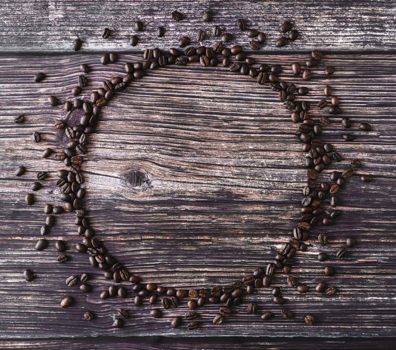 Ram som göras av spillda kaffebönor på en trätabell lantlig st?tta arkivbilder