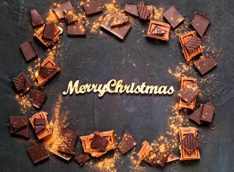 Rama czekolada na ciemnym tle z znaczkiem wesoło boże narodzenia, kopii przestrzeń obraz royalty free