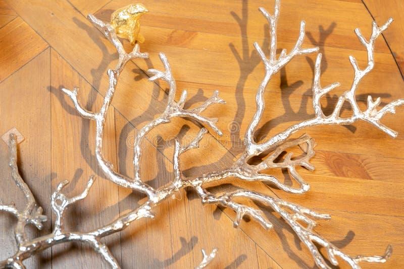 Rama de árbol decorativa de plata que miente en las tejas de mármol con el entarimado, modelo de madera imagen de archivo libre de regalías