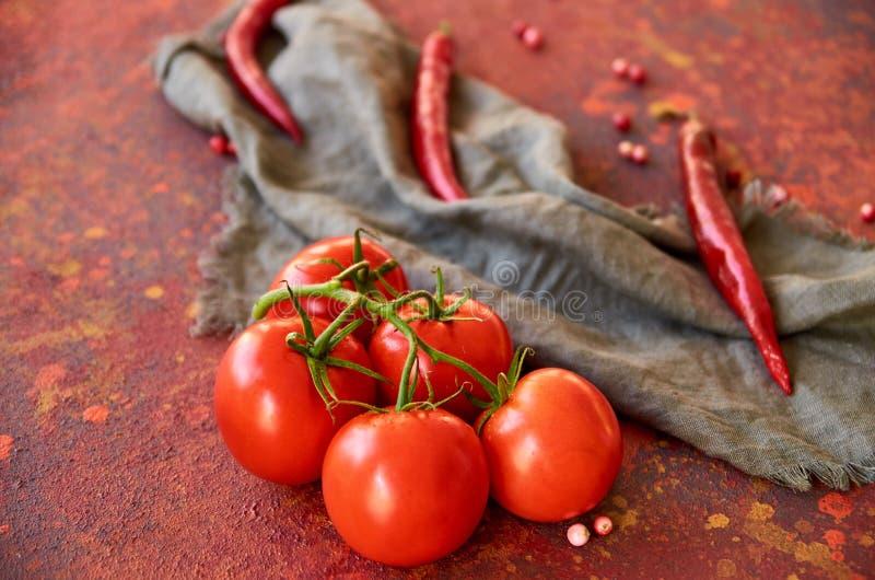 Rama de los tomates rojos aislados en fondo abstracto rojo En las pimientas grises borrosas del paño y de chile del fondo fotos de archivo