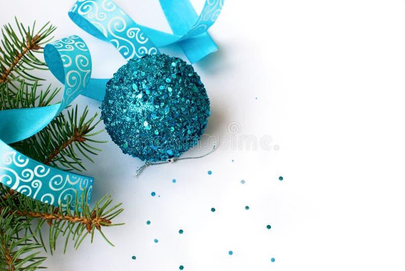 Rama de un árbol de navidad y una bola y una cinta azules imágenes de archivo libres de regalías
