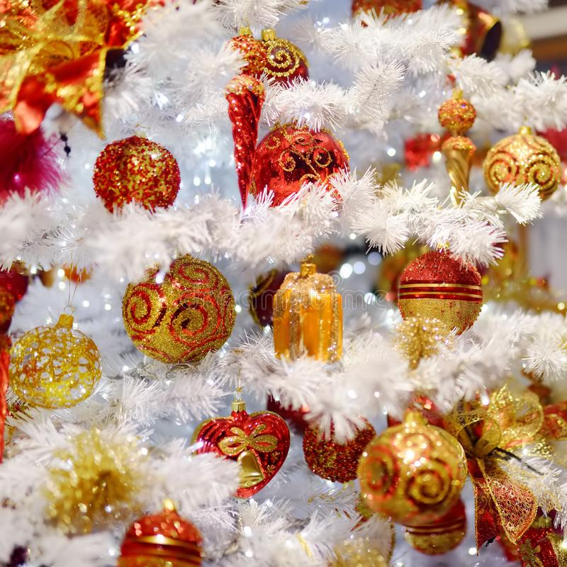 Rama del árbol de navidad artificial blanco adornado con oro y bolas rojas Cierre para arriba imagen de archivo