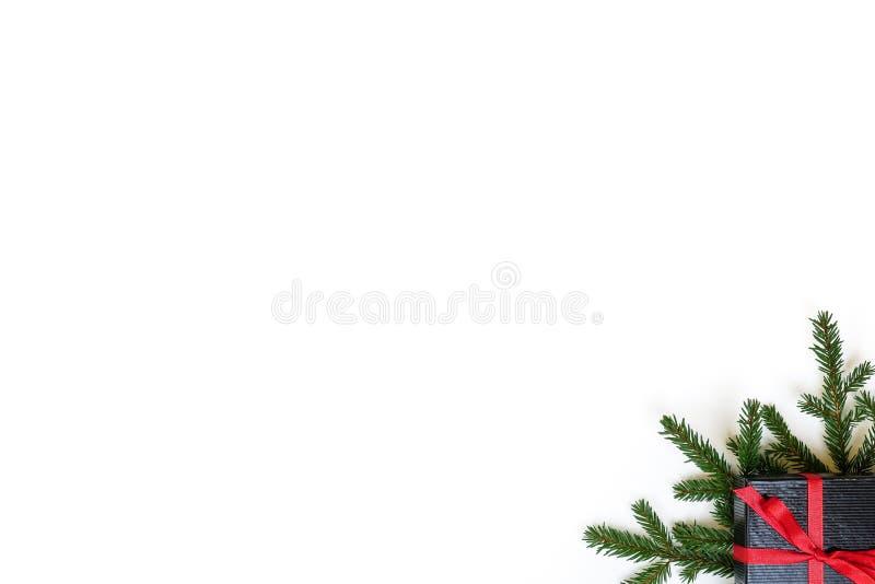 Rama del abeto/ramita y caja de regalo negra de la Navidad en blanco foto de archivo
