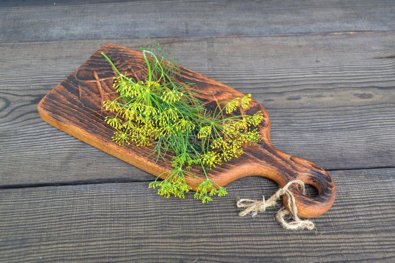 Rama del eneldo verde fresco en tabla de cortar rústica en la tabla oscura del vintage Eneldo en un fondo de madera oscuro tono E imagenes de archivo