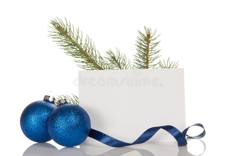 Rama del pino, dos bola-juguetes de la Navidad, tarjeta en blanco, aislada en w imagenes de archivo