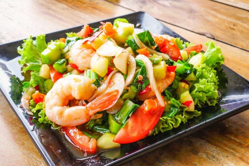 Rama picante de la col rizada con la ensalada del camarón en el plato negro 3 fotos de archivo libres de regalías