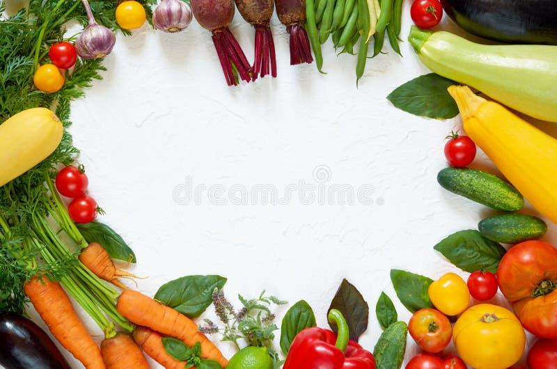 Rama różnorodni jarscy składniki przygotowywający dla gotować na białym stole Organicznie zdrowy jedzenie: kolorowi warzywa, ziel fotografia stock