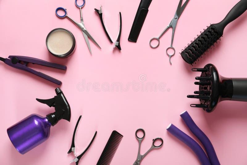 Rama robić nożyce i innego fryzjera akcesoria na różowym tle, mieszkanie nieatutowy zdjęcie stock
