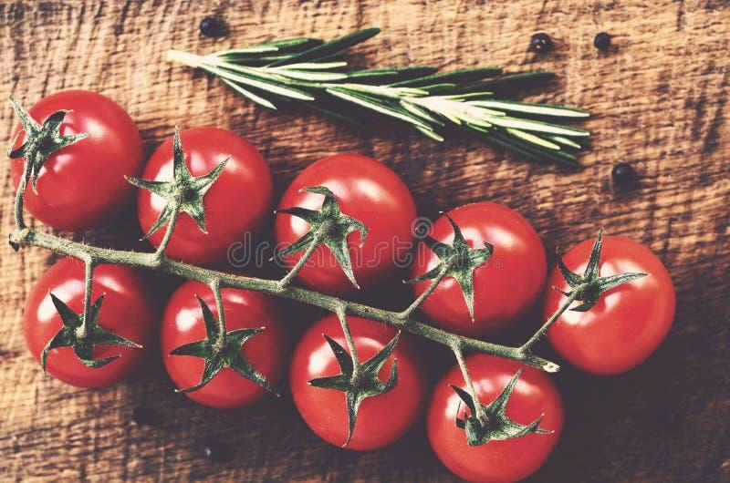 Rama roja del tomate de cereza en la tabla de madera rústica imágenes de archivo libres de regalías