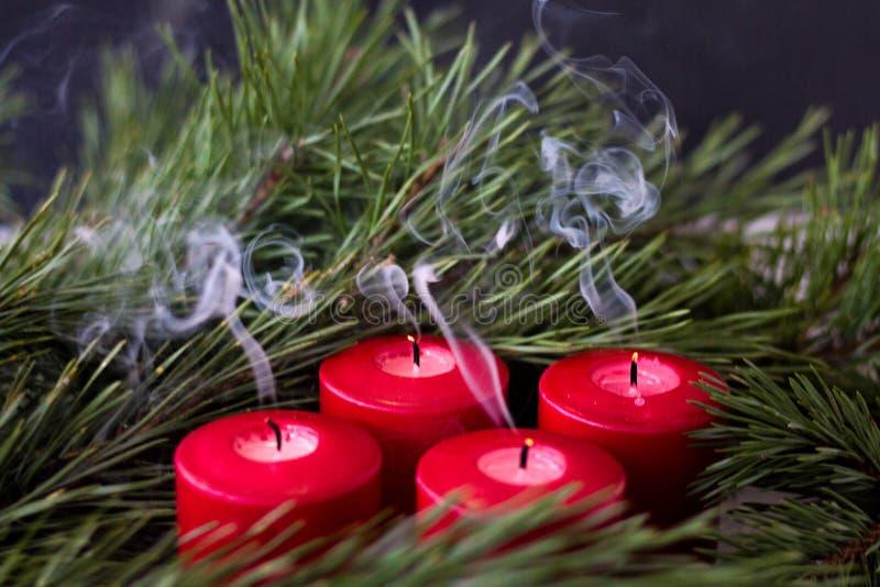 Rama verde Spruce y velas extintas rojas del advenimiento de las cuales el humo viene foto de archivo