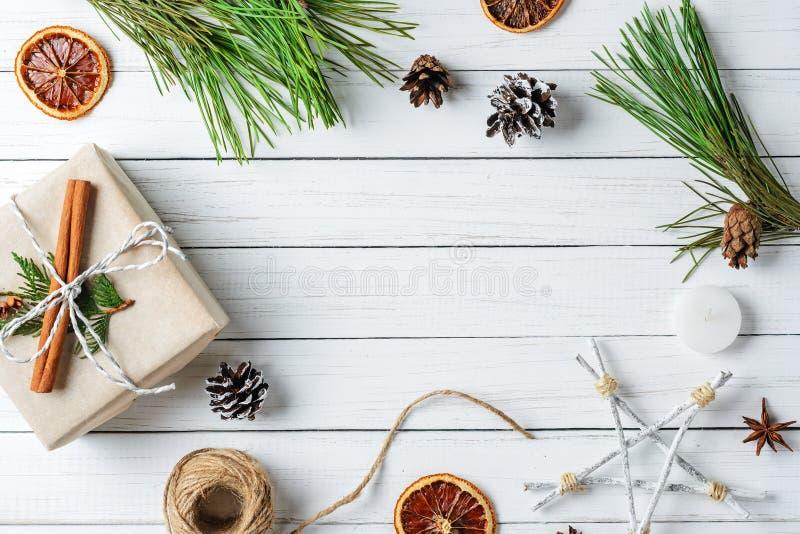 Rama z prezentów pudełkami, sosna rożkami i wysuszonymi pomarańczami na białym drewnianym tle, Cristmas dekoracje zdjęcie stock