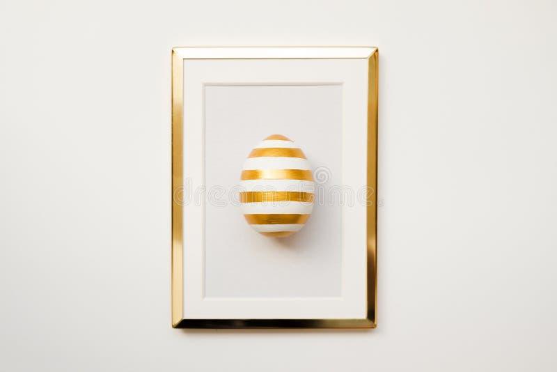 Rama z złotem paskował Easter jajko z kopii przestrzenią dla teksta pojedynczy białe tło Minimalny Szczęśliwy Wielkanocny pojęcie fotografia stock