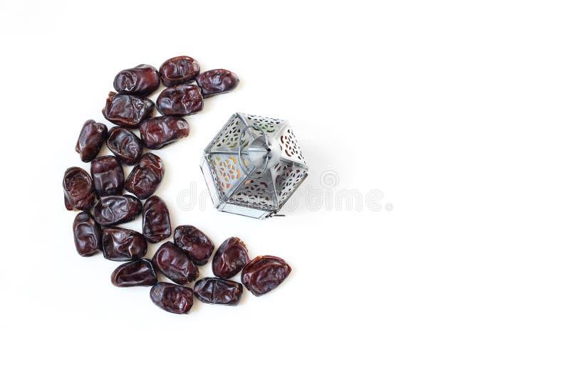 Ramadan, composition en table iftar Fruit de datte sèche disposé dans la lune et la lanterne arabe argentée d'isolement sur le fo photo stock