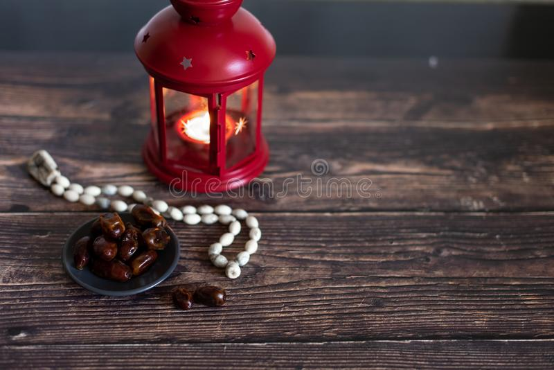 Ramadan concept. Dates close-up in the foreground. Ramadan Lantern on a wooden table. Textured yellow wall background. Space for royalty free stock photo