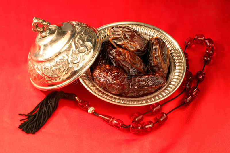 Ramadan dates. A silver bowl containing the finest dates, which are traditionally eaten in Arabia for Iftar to break the Ramadan fast at sundown, next to prayer