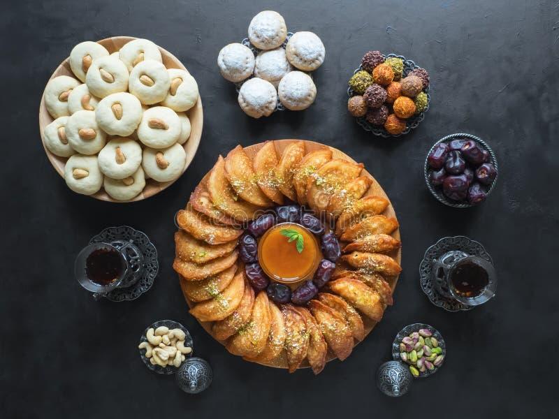 Ramadan food background. Arabic sweets. Arabian Qatayef, Ghorayeba sweets and Egyptian cookies `Kahk El Eid`. Cookies of El Fitr Islamic Feast royalty free stock image