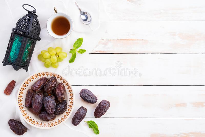 Ramadan food and drinks concept. Ramadan Lantern with tea, dates fruit, grape and Mint leaves on a white wooden table background. royalty free stock photography
