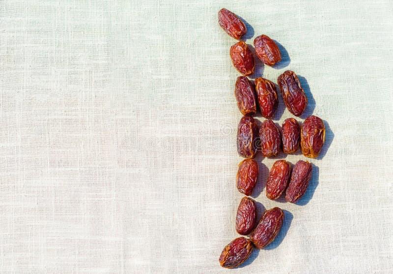 Ramadan Kareem. Dates on vintage tablecloth in the shape of crescent moon. Ramadan Kareem. Dates on tablecloth vintage background  in the shape of crescent moon royalty free stock photo