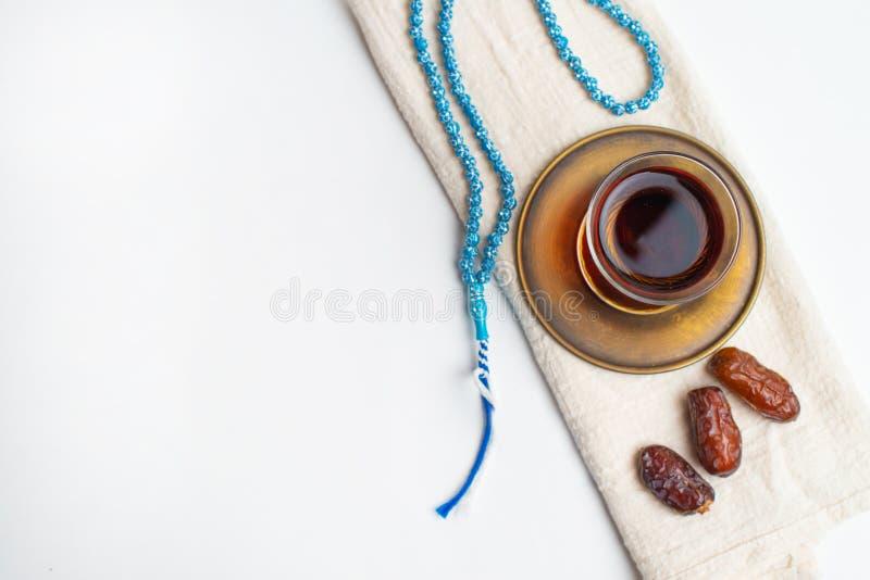 Ramadan Kareem Festival, date sulla ciotola di legno con la tazza di tè nero ed il rosario su fondo isolato bianco immagini stock