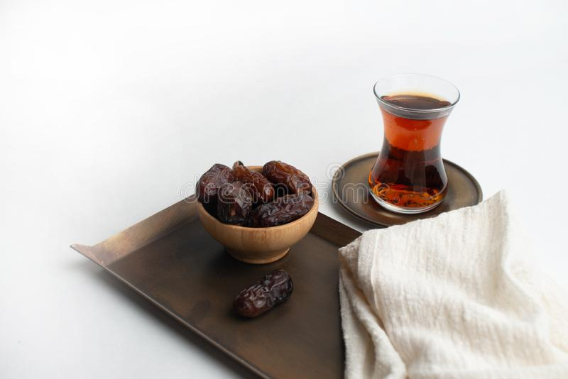 Ramadan Kareem Festival, fechas en el cuenco de madera con la taza de té negro y el rosario en el fondo blanco imagenes de archivo
