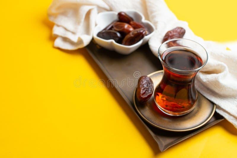 Ramadan Kareem festiwal, daty przy pucharem z filiżanką czarna herbata na żółtym tle zdjęcie royalty free