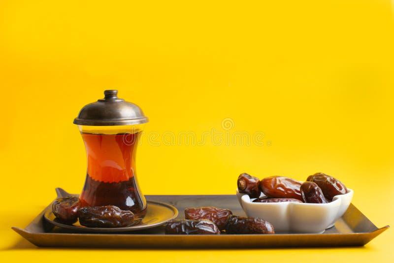 Ramadan Kareem festiwal, daty przy pucharem z filiżanką czarna herbata na żółtym tle obraz royalty free