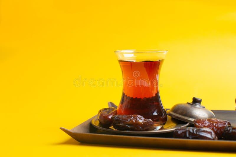Ramadan Kareem festiwal, daty przy pucharem z filiżanką czarna herbata na żółtym tle obrazy stock