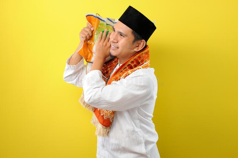 In Ramadan Kareem, Smiling Happy Young Asian Muslim man brings a bug of rice in his shoulder to give for everyone need. Isolated on yellow background stock photo