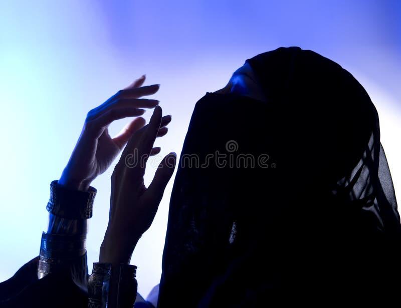 Ramadan: Mooi jong moslimmeisje die, Donker silhouet bidden stock foto