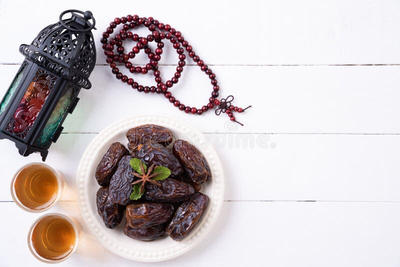 Ramadan-Nahrung und Getr?nkkonzept Ramadan Lantern mit arabischer Lampe, hölzernes Rosenbeet, Tee, Dattelfrucht auf einem weißen  lizenzfreie stockfotos