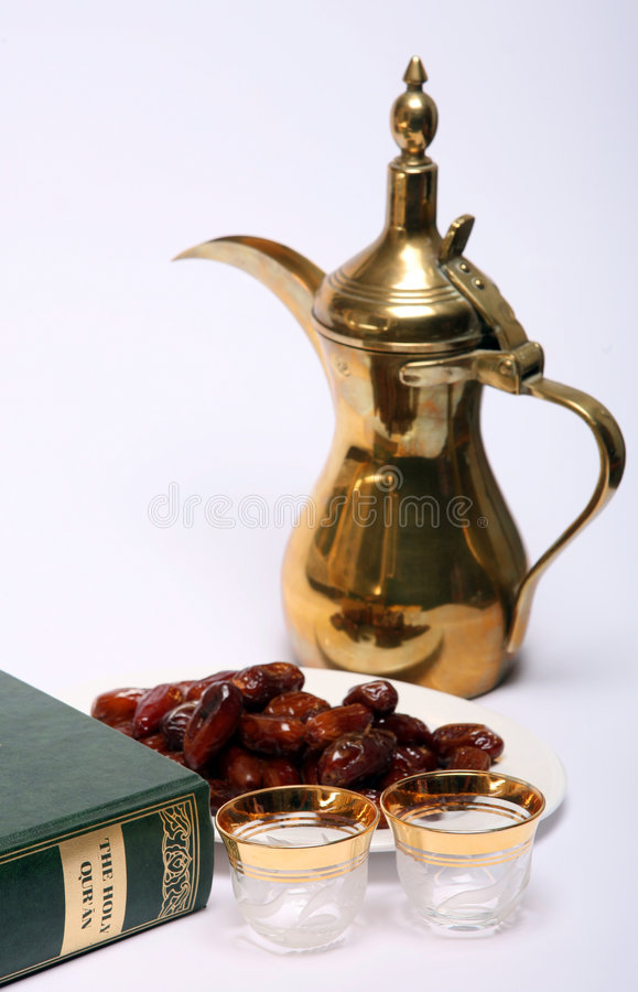 Ramadan scene. Dates, coffee jug and cups waiting to be filled and a copy of the Holy Qur'an, all are symbolic of the Muslim fasting month of Ramadan and of the