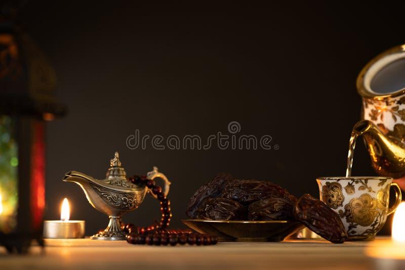 Ramadanmat och drinkbegrepp Ramadan Lantern med den arabiska lampan, träradbandet, te, datumfrukt och belysning på en trätabell arkivbilder