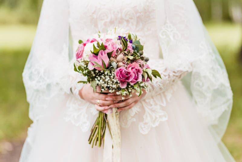 Ramalhete à moda delicado das rosas nas mãos da noiva fora imagens de stock