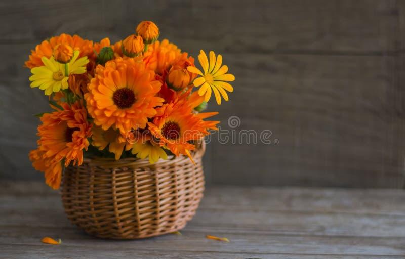 Ramalhete alaranjado de flores do cravo-de-defunto em uma cesta em um fundo de madeira com uma cópia do espaço foto de stock royalty free