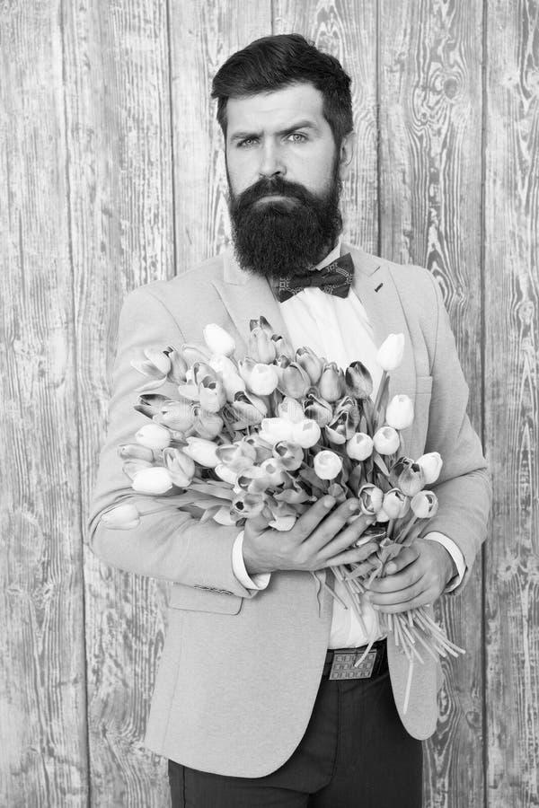 Ramalhete bem preparado das flores da posse do la?o do smoking do desgaste do homem Convide-a que data Homem rom?ntico com flores fotos de stock
