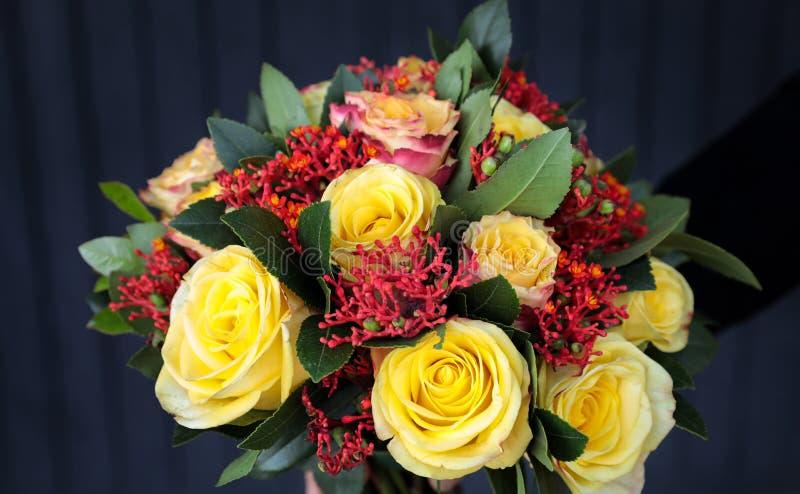 Ramalhete bonito à moda em cores amarelas e corais das rosas, do multifida do Jatropha e das outras plantas na mão do florista fotos de stock royalty free