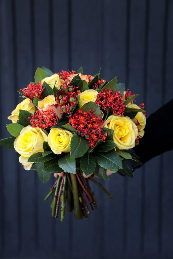 Ramalhete bonito à moda em cores amarelas e corais das rosas, do multifida do Jatropha e das outras plantas na mão do florista imagens de stock royalty free