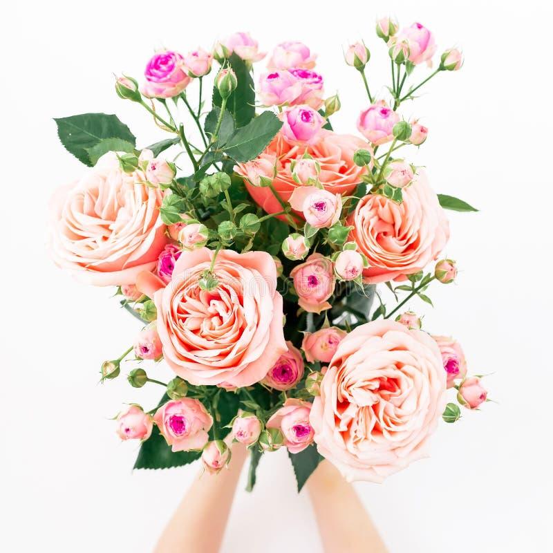 Ramalhete bonito com as rosas cor-de-rosa nas mãos no fundo branco Configuração lisa, vista superior Composição do dia de Valenti fotos de stock royalty free