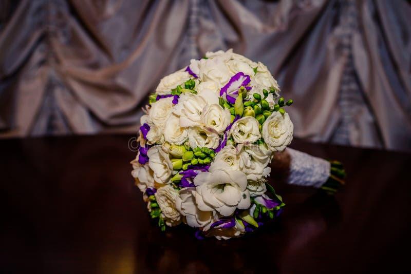 Ramalhete bonito com flores da frésia, ramalhete das flores do casamento e Eustoma, isolados na tabela de madeira Flores de Lisia fotos de stock