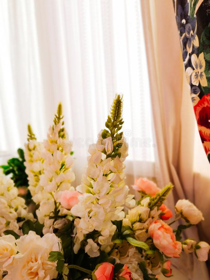 Ramalhete bonito das flores com lupines em um vaso no fundo das cortinas e o tule branco na sala de visitas ou no quarto imagem de stock