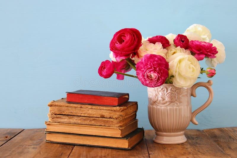 Ramalhete bonito das flores no vaso ao lado dos livros velhos fotos de stock royalty free