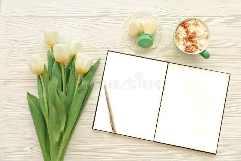 Ramalhete bonito das tulipas brancas, caderno aberto vazio, pena de prata, copo do cappuccino, makaroons no fundo de madeira bran foto de stock