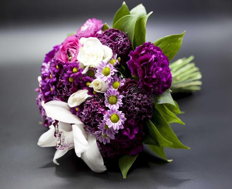 Ramalhete bonito de flores roxas da noiva em um fundo escuro foto de stock