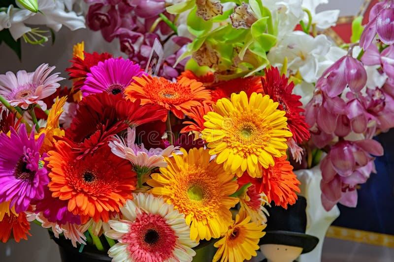 Ramalhete bonito de gerberas vermelhos em um vaso de vidro no mercado da flor Fim acima foto de stock