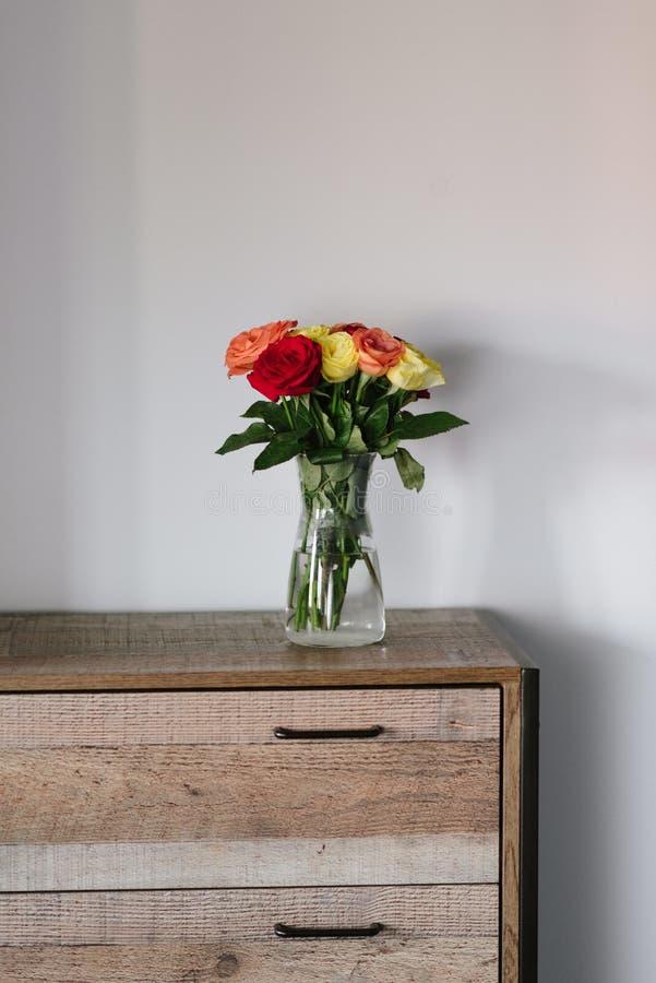 Ramalhete bonito de rosas coloridas em um frasco de vidro em um armário de madeira imagem de stock