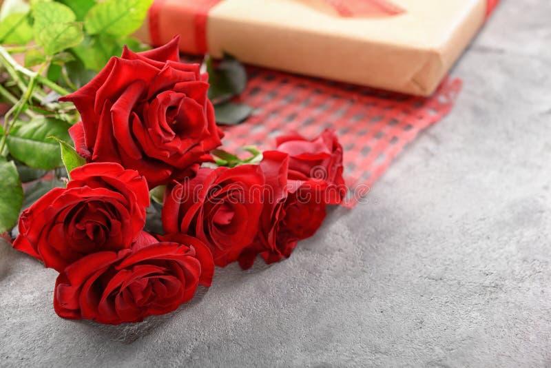 Ramalhete bonito de rosas vermelhas e de caixa de presente no fundo cinzento imagens de stock royalty free