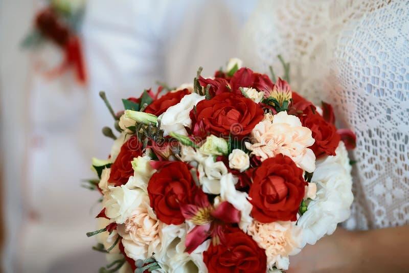 Ramalhete bonito do casamento com as flores brancas e vermelhas nas mãos dos noivos, acessórios do casamento imagem de stock