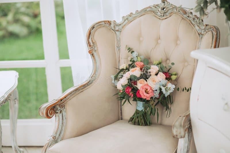 Ramalhete bonito do casamento da mola das rosas e do eucalipto em uma poltrona bege do vintage fotos de stock royalty free